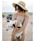 девушка на пляже держит щенка